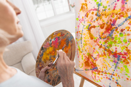 Tender senior female hand using palette while holding tassel and easel standing with picture Stock Photo