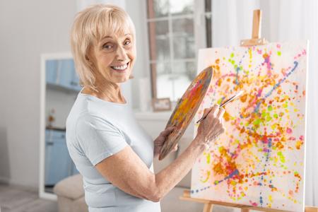 Nette fröhliche reife Frau , die Palette und Quaste beim grinsend und Kamera betrachtet Standard-Bild - 95999898