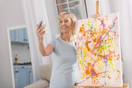 Talented nice mature woman using phone for shooting and easel standing