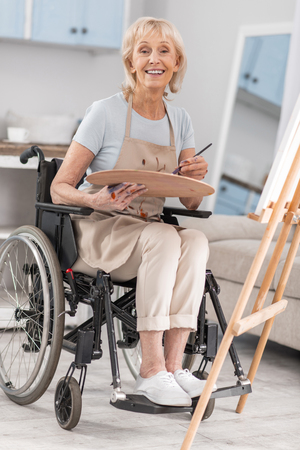 Disabled mature nice woman posing in wheelchairs while grinning and carrying pallet and tassel