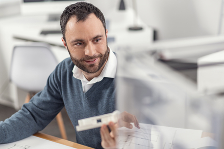 Cutting-edge technologies. The focus being on a handsome young engineer sitting at his work desk in the office, holding a model and looking at a 3D printer with a content smile Stock Photo