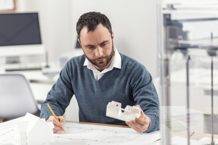 Necessary corrections. Pleasant young engineer sitting at the work desk and changing his blueprint according to a 3D model, having printed it with a 3D printer