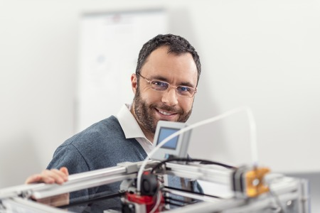 Love useful technologies. Pleasant upbeat young engineer in eyeglasses posing for the camera while standing near a 3D printer and resting one of his hands on its body