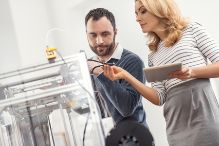 Best quality. Pretty female supervisor holding a tablet with one hand and checking the quality of wires of a 3D printer with the other hand while her male colleague watching her