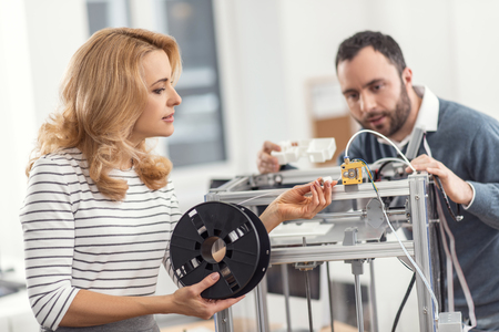 Necessary supply. Pleasant young woman connecting filament to a 3D printer, fixing a problem caused by the shortage of the material