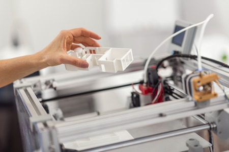 Best replica. The close up of a delicate female hand removing a house model from a 3D printer, having printed it for her project Archivio Fotografico