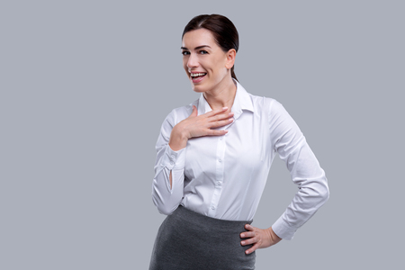 Overjoyed. Nice happy dark-haired young woman wearing a white shirt and smiling and having her hand on her breast