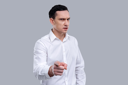 Being strict. Good-looking stern dark-eyed young man wearing a white shirt and pointing with his finger and having austere look Stock Photo