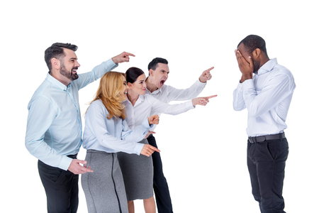 Mocking. Attractive stylish young co-workers mocking and pointing at their afro-american colleague and he covering his face with fingers Stock Photo