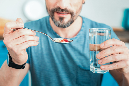 Useful colorful pills lying in the spoon which man holding. Stock Photo