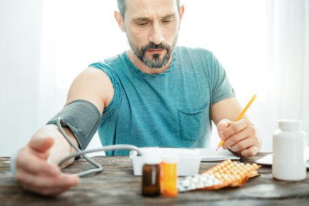 Sad disappointed deep man measuring pulse by the table looking down and recording results.