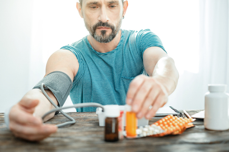 Thoughtful ill unshaken man sitting by the table taking pills measuring his pulse.