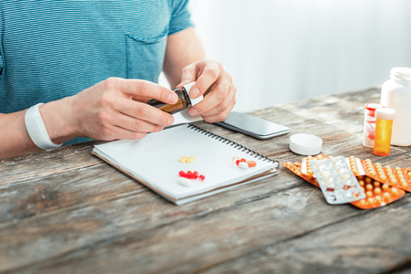 Responsible attentive man sitting by the table holding a jar and decomposing pills on the notebook.