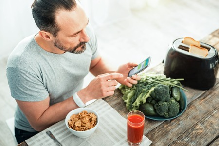 Concentrated careful unshaken man sitting in the kitchen by the table using his cellphone preparing for eating.