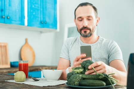 Calm pleasant concentrated man sitting in the room by the table using his cellphone touching a broccoli.