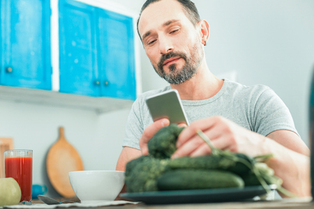 Satisfied smart man spending time in the kitchen taking vegetables and using the cellphone.