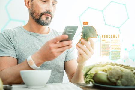Handsome interested occupied man standing with the cellphone in his hand holding and examining a broccoli.