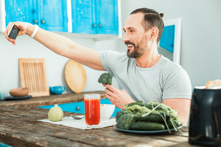 Pleasant happy man sitting in the kitchen by the table holding a broccoli and making selfie.