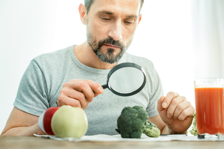 Serious curious interested man sitting in the bright room looking through the magnifying glass at a broccoli and focusing on it.
