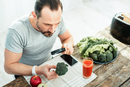 Interested attentive calm man sitting by the table holding the magnifying glass and overlooking a broccoli.