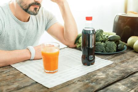 Dos bebidas diferentes están en la mesa, una frente a la otra, cerca de un hombre.