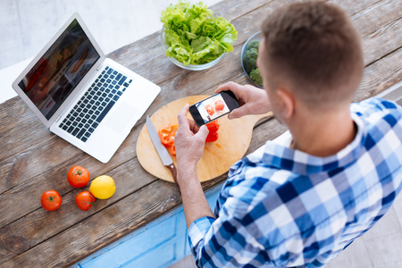 Top view of confident earnest man taking photo while using smartphone and eating healthy food