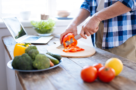 Close up of young male hands slicing red bell pepper for cooking salad and holding knife Stock Photo