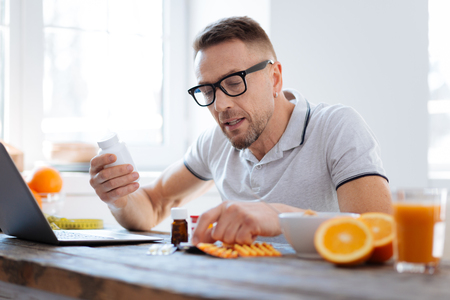 Handsome progressive doubtful man deciding about biohacking supplements while sitting and improving his health