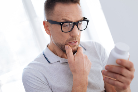 Intelligent pensive appealing man placing hand on chin while reading and holding bottle