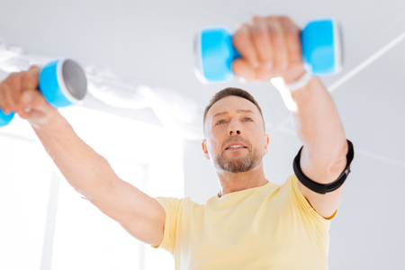 Low angle of strong pensive determined man smiling while using dumbbells and working out