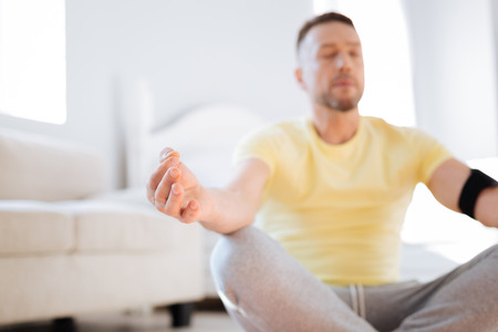 Selective focus of male hand resting on knee while relaxing and practicing meditation