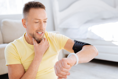 Bearded cheerful skillful man touching neck while using fitness watch and looking down Stock Photo