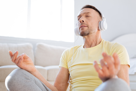 Charming energetic nice man posing while enjoying music and trying mediation