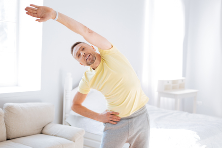 Energetic positive pretty man leaning to left while opening mouth and exercising