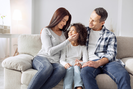Attractive alert curly-haired girl smiling and sitting on the couch with her parents and they looking at her