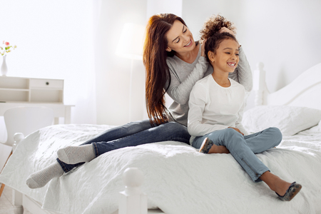 Attractive cheerful dark-haired woman smiling and making a hairdo for her daughter while sitting on the couch