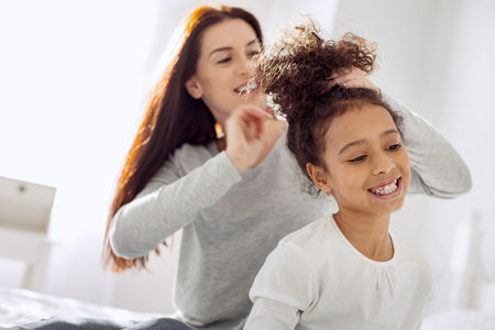 Beautiful happy curly-haired girl smiling and her mother standing behind her and making a hairdo for her