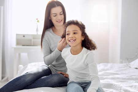 Nice joyful curly-haired girl smiling and her mother sitting behind her and making a hairdo for her
