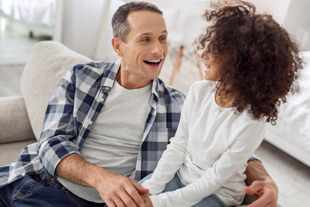 Good-looking inspired dark-haired man smiling and talking with his daughter and they looking at each other