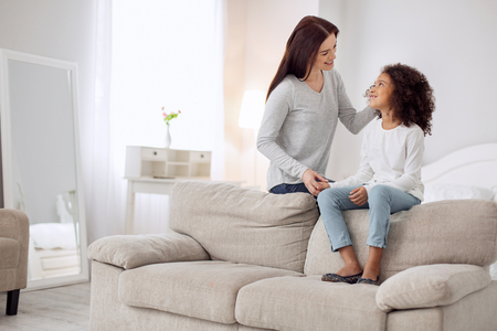 Beautiful happy young long-haired woman smiling and looking at her daughter and caressing her Stock Photo