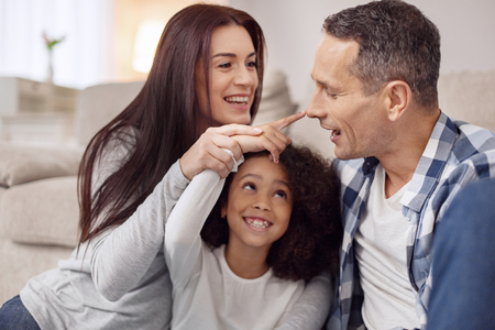 Pretty content young long-haired woman smiling and sitting on the floor with her husband and daughter and they touching the man on the nose Stock Photo