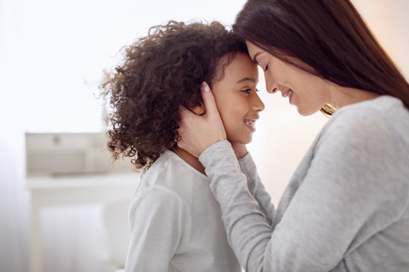 Beautiful content young long-haired mother smiling and hugging her daughter and the girl looking at her Stock Photo