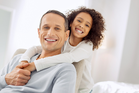 Good-looking alert dark-haired father sitting in the arm-chair and smiling and his daughter standing behind him Stock Photo