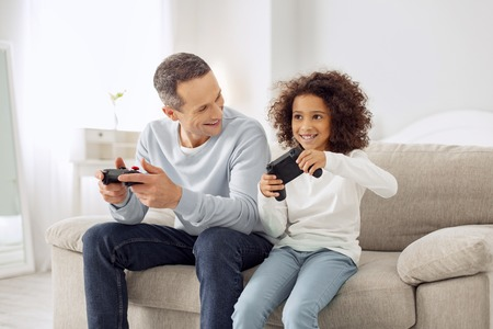 Beautiful happy curly-haired girl smiling and playing games with her father while sitting on the couch