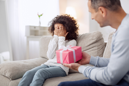 Happy lovely curly-haired girl sitting on the sofa and closing her and her daddy holding a gift Archivio Fotografico