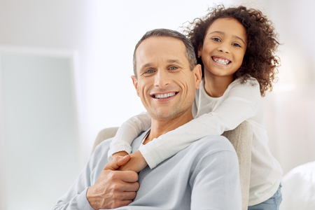 Attractive joyful dark-haired father sitting in the arm-chair and smiling and his daughter standing behind him