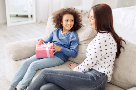 Attractive content curly-haired girl smiling and holding her gift while looking at her mother sitting near her Stock Photo