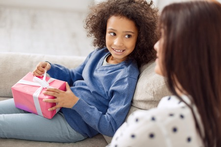 Pretty content curly-haired girl smiling and holding her gift while looking at her mother sitting near her