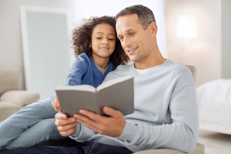 Attractive cheerful dark-haired reading a book and the girl sitting near him and smiling