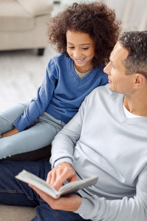 Pretty happy curly-haired girl smiling and sitting near her father and her daddy holding a book 스톡 콘텐츠